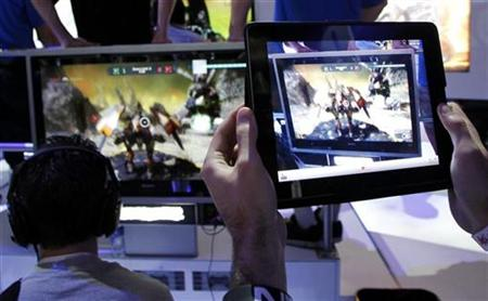 "A man uses an Apple iPad to record a man playing ""Star Hawk"" on the PS3 during E3 in Los Angeles"