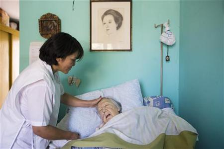 An elderly woman who is terminally ill receives attention in a room at the senile dementia building at the Canevaro old people's home in Lim