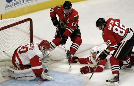 Detroit Red Wings goaltender Chris Osgood (L) makes a point-blank save on Chicago Blackhawks center Jonathan Toews (2nd L) while Red Wings defenseman Brad Stuart (2nd R) and Blackhawks winger Tomas Kopecky close in during the third period of their NHL hockey game in Chicago October 9, 2010. REUTERS