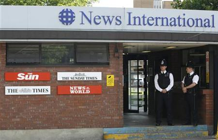 Police officers stand outside an entrance to News International in London
