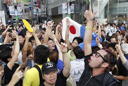 Japan soccer fans celebrate on a street in Tokyo after Japan beat the U.S. in their Women's World Cup final soccer match in Frankfurt
