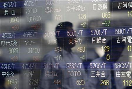Passers-by are reflected in a stock index board outside of a brokerage in Tokyo