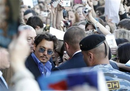 "Actor Depp is surrounded by fans and security after arriving for the premiere of his new film ""Pirates of the Caribbean:On Stranger Tides"" a"