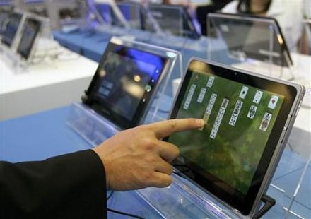 A visitor plays with a tablet PC at the Intel booth during the Computex 2011 computer fair at the TWTC Nangang exhibition hall in Taipei