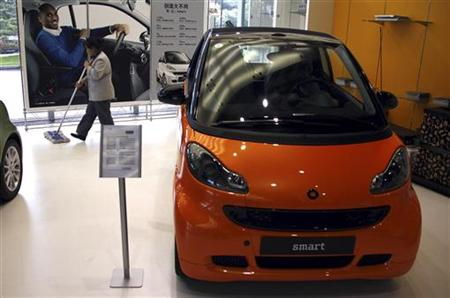 A cleaner walks past a Smart car displayed in front of a poster featuring U.S. NBA basketball superstar Kobe Bryant in a showroom in Beijing