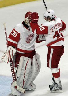 Detroit Red Wings goaltender Chris Osgood (L) is congratulated by Henrik Zetterberg after defeating the Chicago Blackhawks in their NHL hockey game in Chicago October 9, 2010. REUTERS