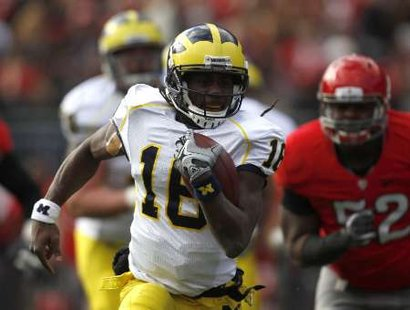 Michigan quarterback Denard Robinson (16) runs the ball by Ohio State defender Johnathan Hankins (52) during the second quarter of their game in Columbus, Ohio, November 27, 2010. REUTERS