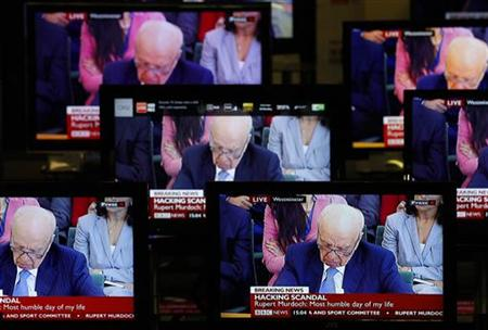 News Corp Chairman and Chief Executive Rupert Murdoch is seen on television screens in an electrical store as he is questioned by a parliame