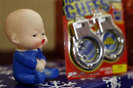 A baby doll and a pair of plastic handcuffs are seen on display at a news conference in Washington