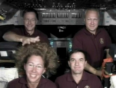 Space shuttle Atlantis Commander Chris Ferguson reaches in to tame the zero-G hairdo of fellow astronaut Sandy Magnus.