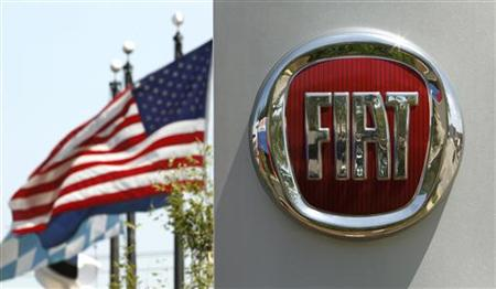 A U.S. flag flutters in the wind behind a Fiat logo at a car dealership in Alexandria