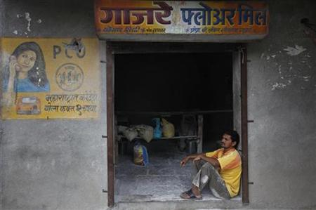 An employee sits outside a flour mill in the Ralegan Siddhi village, located in the Ahmednagar district about 250km (155 miles) south east o