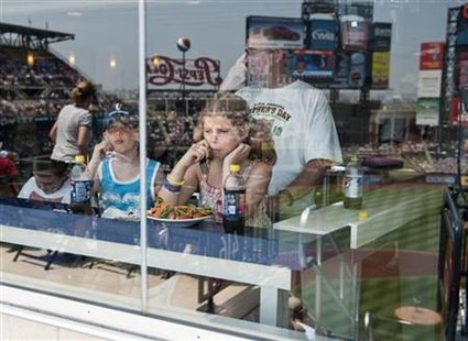 The stadium is reflected in the glass as young fans sit in an air-conditioned resturaunt as the New York Mets play the St. Louis Cardinals i