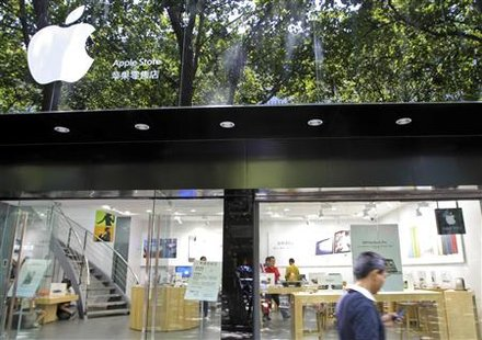 A pedestrian uses his cell phone as he walks past a fake Apple store in Kunming, Yunnan province