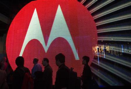 People pass by the Motorola booth during the 2011 International Consumer Electronics Show (CES) in Las Vegas