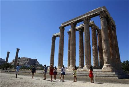 Tourists walk past the Temple of the Olympian Zeus in Athens