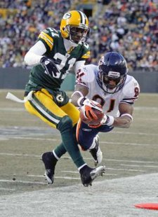 Chicago Bears' Rashied Davis (81) dives for the first down against Green Bay Packers' Charles Woodson, (21) late in the first half during their NFL football game in Green Bay, Wisconsin January 2, 2011. REUTERS