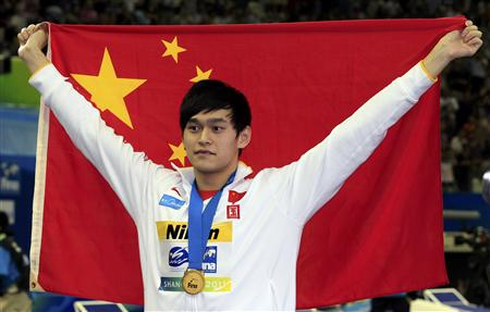China's Sun poses with his gold medal and national flag after men's 1500m freestyle final at 14th FINA World Championships in Shangha