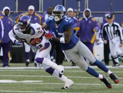 New York Giants wide receiver Plaxico Burress (R) tries to tackle Minnesota Vikings safety Dwight Smith (24) after he intercepted a pass from Giants quarterback Eli Manning in the second quarter of their National Football League game in East Rutherford, New Jersey, November 25, 2007. REUTERS/Ray Stubblebine (UNITED STATES)