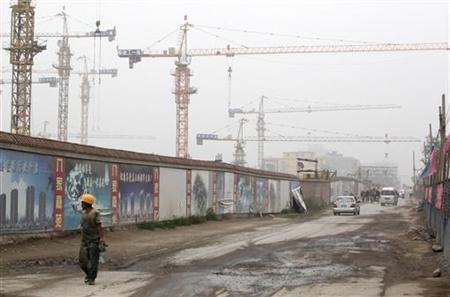 A worker walks past a residential construction site in Beijing