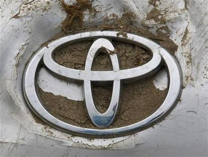A Toyota logo on a damaged car is seen at a dump site for tsunami debris near Sendai airport