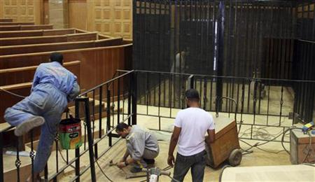 Workers prepare a cage enclosure in a courtroom for the upcoming trial of former Egyptian President Mubarak in Cairo