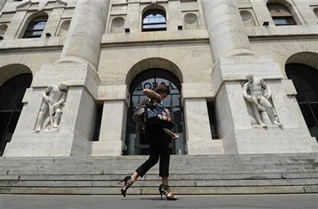 A woman walks past Milan Stock Exchange