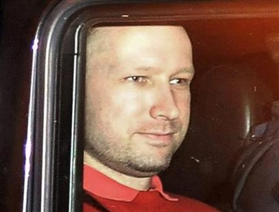 Norwegian Breivik, man accused of a killing spree and bomb attack in Norway, sits in the rear of a vehicle as he is transported in a police