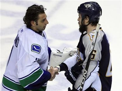 Nashville Predators defenseman Shea Weber shakes hands with Vancouver Canucks goalie Roberto Luongo after losing following Game 6 of the NHL