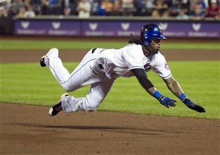 New York Mets Jose Reyes dives into third base as he hits triple against Oakland Athletics in New York