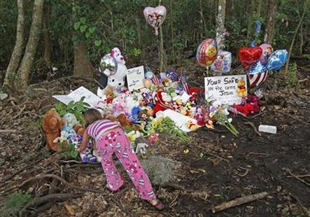 An unidentified young girl places a toy bear at the wooded location of where the body of Caylee Anthony was found in 2008, in Orlando