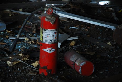 A used fire extinguisher sits outside.