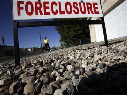 A man stands in front of a foreclosed home in Bullhead City, Arizona