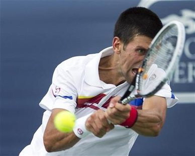 Serbia's Djokovic hits return to Russia's Davydenko at the Rogers Cup tennis tournament in Montreal