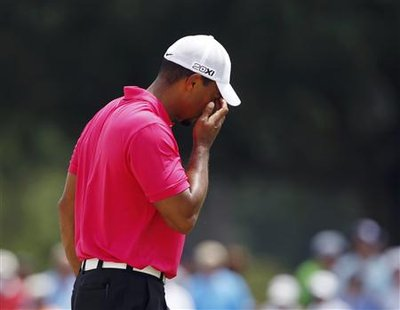 Tiger Woods of the U.S. wipes sand from his eyes after hitting from a sand trap on the ninth hole during the first round of the 93rd PGA Cha