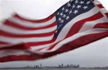 A U.S. flag flutters over top of the skyline of New York and Jersey City, as seen from Bayonne