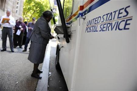 On the deadline day for US citizens to file their income tax returns, a woman stands at the front of the line at a mobile post office near t