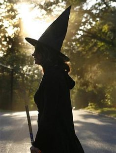 A woman dressed as a witch walks along the street during Halloween celebrations in Port Washington