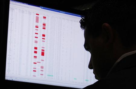 A trader is silhouetted against his computer screen as he works on the floor of the New York Stock Exchange in New York