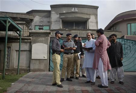 Police and security officials gather outside the residence of an American citizen after he was kidnapped in Lahore