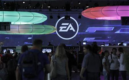 Visitors walk past the exhibition stand of Electronic Arts at the Gamescom 2010 fair in Cologne