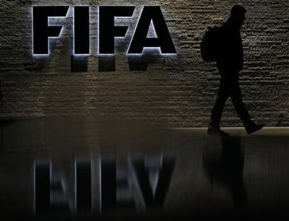 File photo of a silhouetted man walking past the main entrance of FIFA headquarters the Home of FIFA in Zurich
