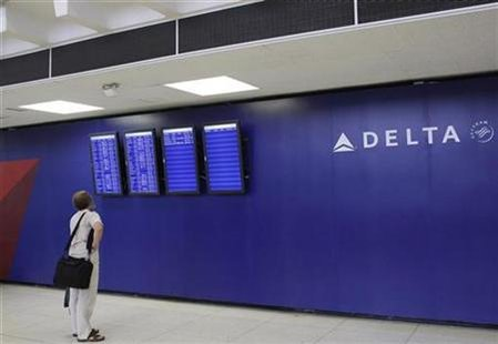 A man looks at a monitor for arrival and departure flight information at the Delta airline terminal at JFK Airport in New York