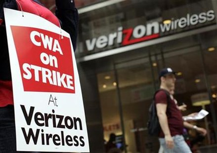 A striking Verizon worker walks the picket line in front of a Verizon wireless store in New York