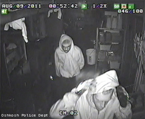 This still frame taken from surveillance video shows two people Oshkosh police say burglarized buildings on the city's west and north sides, Aug. 9, 2011.