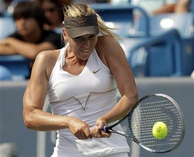 Sharapova of Russia hits a return to compatriot Kuznetsova during their third round match of the 2011Cincinnati Open tennis tournament