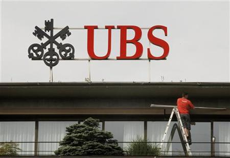 A worker stands on a ladder under the logo of Swiss bank UBS at the company's headquarters in Zurich