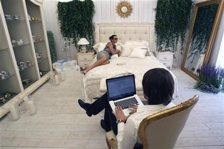 A man sits with his computer at a furniture and chinaware booth during the Summer Fair in Moscow