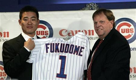 Former Japanese baseball player Kosuke Fukudome shows his new jersey with Chicago Cubs general manager Jim Hendry during a news conference i