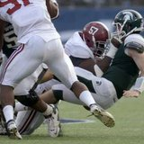 Michigan State Spartans quarterback Andrew Maxwell (R) is sacked by Alabama Crimson Tide defensive end Marcell Dareus (57) during the second half of their Capital One Bowl college football game in Orlando, Florida, January 1, 2011. REUTERS/Phelan M. Ebenhack (UNITED STATES - Tags: SPORT FOOTBALL)